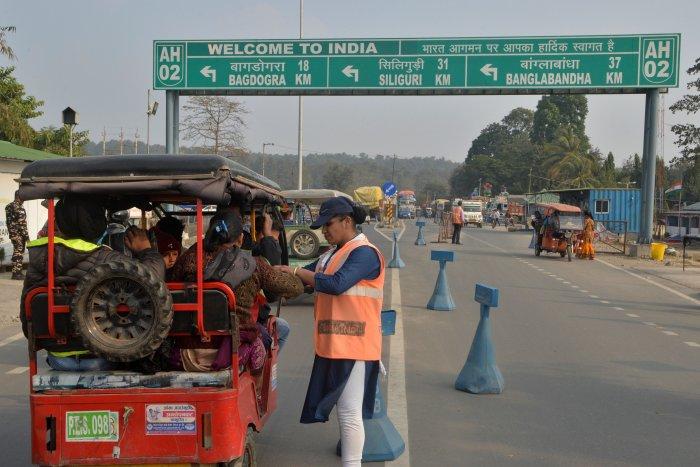 An Indian Sashastra Seema Bal (SSB) personal checks travellers coming from Nepal to India during a Corona virus information camp at an India-Nepal border crossing. (AFP Photo)