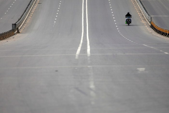 A man rides on an empty street as long distance bus and land border crossings are shut down amid concerns about the spread of coronavirus disease (COVID-19), in Kathmandu, Nepal. (Reuters Photo)