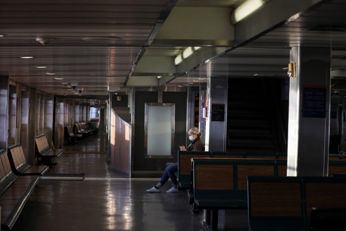 A commuter on the Staten Island Ferry wears a protective face mask and sits alone during the outbreak of the coronavirus disease (COVID-19) in Manhattan. (Credit: Reuters)