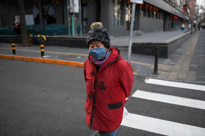 A woman wears a mask as a preventive measure against the COVID-19 coronavirus as she crosses a road in Beijing on March 9, 2020. Credit: AFP Photo