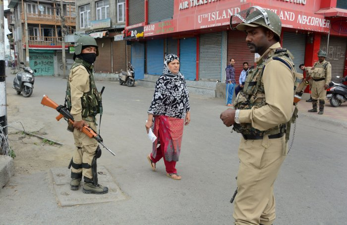 Security personnel stand guard in a market during restrictions after the abrogration of Article 370 and bifurcation of State, in Srinagar