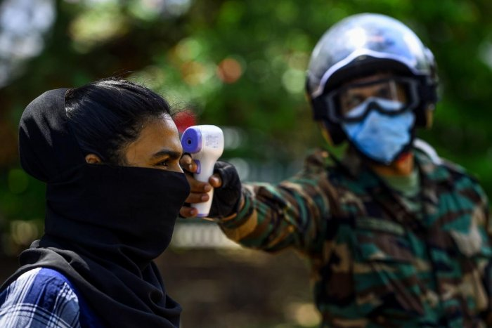 A security personnel (R) checks the body temperature of a pedestrian during a government-imposed nationwide lockdown as a preventive measure against the COVID-19 coronavirus, in Colombo on April 23, 2020. Credit: AFP Photo