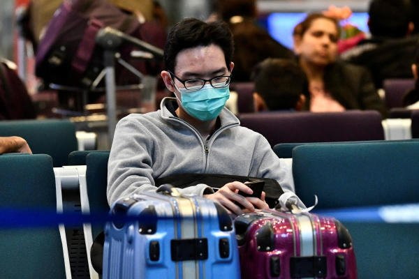 A traveller wearing a mask, sits at Vancouver International Airport (YVR) as Canada's Public Health Agency added a screening question for visitors and began displaying messages in several airports urging travellers to report flu-like symptoms in efforts to prevent any introduction of coronavirus, in Richmond, British Columbia, Canada January 24, 2020. (Reuters Photo)