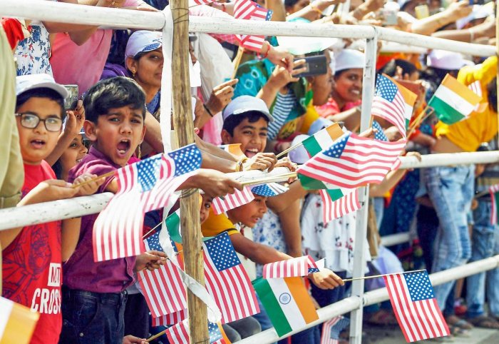 Children wave US and Indian flags as they welcome US President Donald Trump and First Lady Melania Trump during a roadshow in Ahmedabad, Monday, Feb. 24, 2020. Trump is on a two-day visit to India. (PTI Photo)