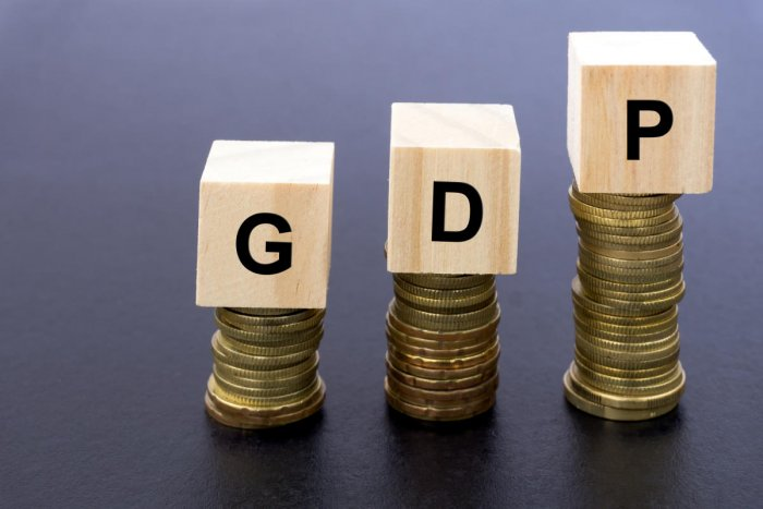 GDP Stand For Gross Domestic Product Word on Wood Block on Top of Coins Stack With Black Background.GDP