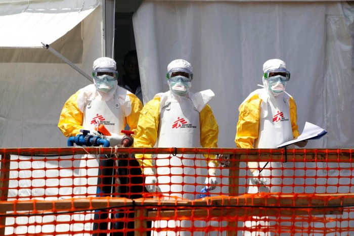 Health workers dressed in protective suits. Photo by REUTERS