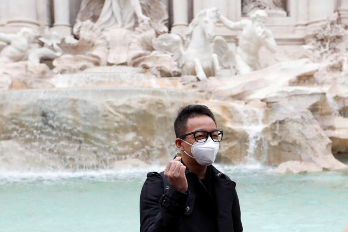 A tourist wearing protective masks waits to throw a coin to the Trevi's Fountain after two cases of coronavirus were confirmed in Italy