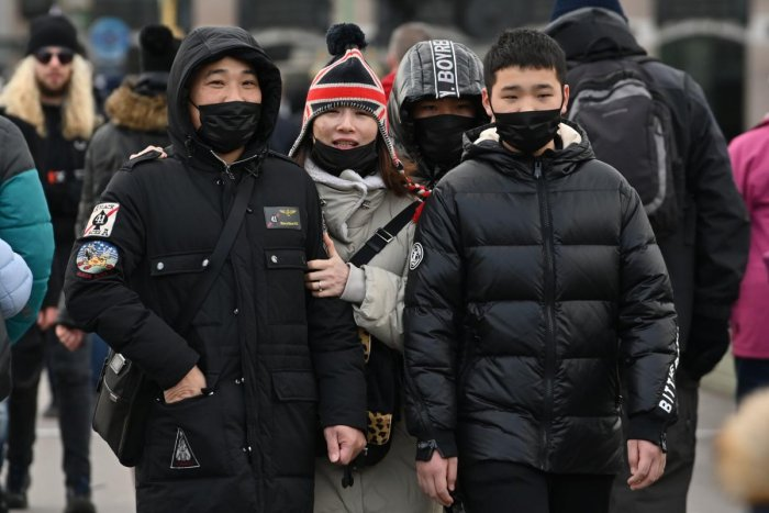 Pedestrians wear face masks as they walk in central London on January 28, 2020
