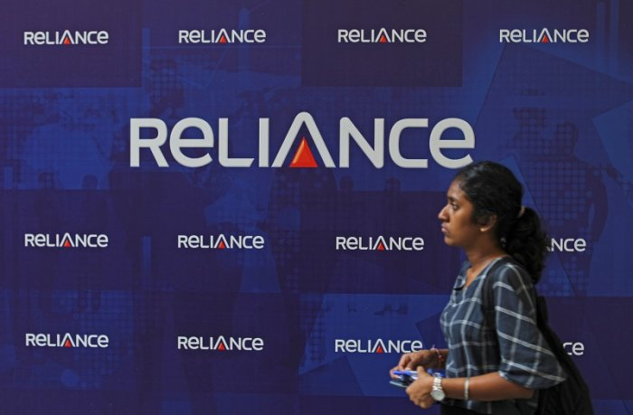 A woman walks past the logos of Reliance Anil Dhirubhai Ambani Group during the company's annual general meeting in Mumbai, India. (PTI Photo)