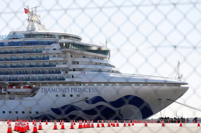 The Diamond Princess, where many passengers have tested positive for coronavirus, is seen through steel fence at Daikoku Pier Cruise Terminal in Yokohama. Credit: Reuters Photo