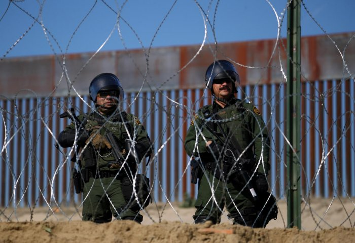 Members of a US border patrol stand near the border fence between Mexico and the United States as migrants stand near by in Tijuana, Mexico, November 25, 2018. (REUTERS)