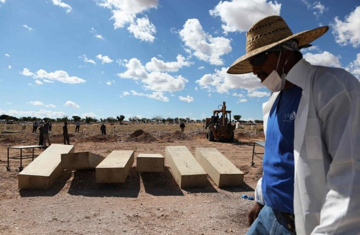A judicial worker walks past coffins with unclaimed corpses (AFP Photo)