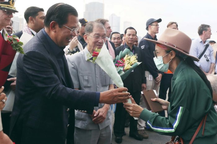 Cambodia's Prime Minister Hun Sen, left, gives a bouquet of flowers to a passenger who disembarked from the MS Westerdam, owned by Holland America Line, at the port of Sihanoukville, Cambodia, Friday, Feb. 14, 2020. Hundreds of cruise ship passengers long stranded at sea by virus fears cheered as they finally disembarked Friday and were welcomed to Cambodia. AP/PTI Photo