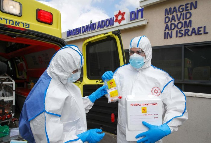 Israeli Paramedics of Maguen David Adom (Israel's National Emergency Pre-Hospital Medical Organisation) at the coronavirus national operations center, gear up with protective clothing during a coronavirus response training exercise in the central Israeli city of Kiryat Ono on February 26, 2020.