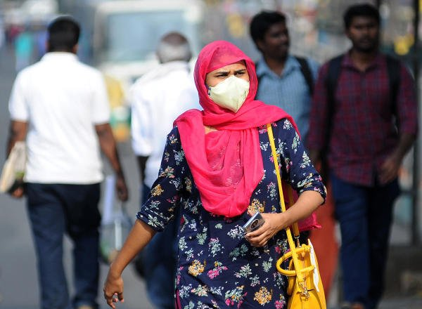 A woman with a mask on seen at Bengaluru Majestic BMTC Bus Stand in wake of COVID-19 outbreak in Bengaluru on Saturday. (DH Photo/ Pushkar V)