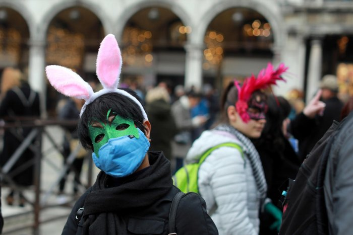 A carnival reveller wears a protective mask at Venice Carnival, which the last two days of, as well as Sunday night's festivities, have been cancelled because of an outbreak of coronavirus, in Venice. Crdit: Reuters Photo