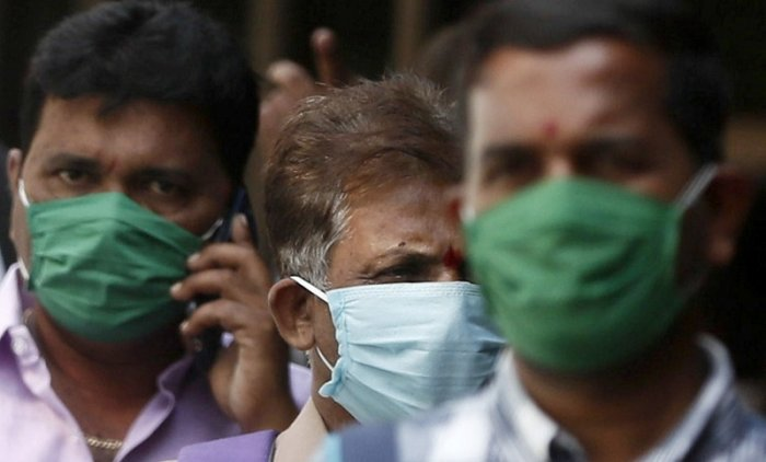 Men wearing protective masks walk inside the premises of a hospital where a special ward has been set up for the coronavirus disease in Mumbai. (Reuters Photo)