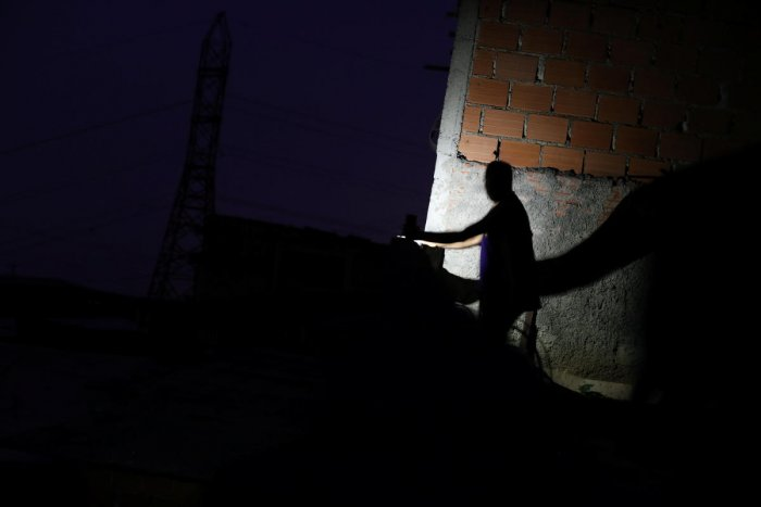 A man uses light from a cellphone at a neighborhood during a blackout in Caracas. Reuters