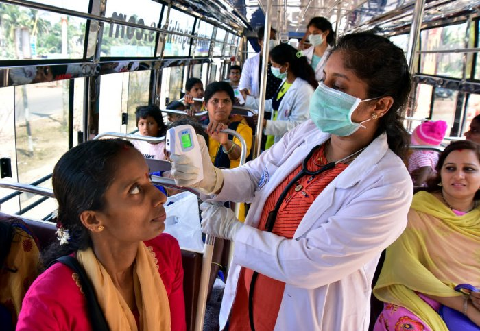 Doctors screen passengers in a bus at Talapady checkpost.
