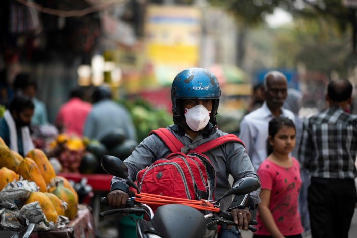 A man (C) wearing a facemask as a preventive measure against the COVID-19 coronavirus rides a motorbike along a street in New Delhi. (AFP Photo)