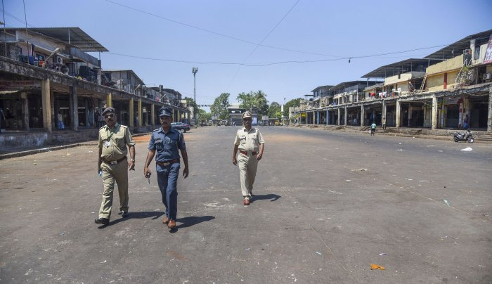 Police personnel patrol a deserted street of APMC market after it was closed in wake of coronavirus outbreak, in Navi Mumbai. (Credit: PTI)