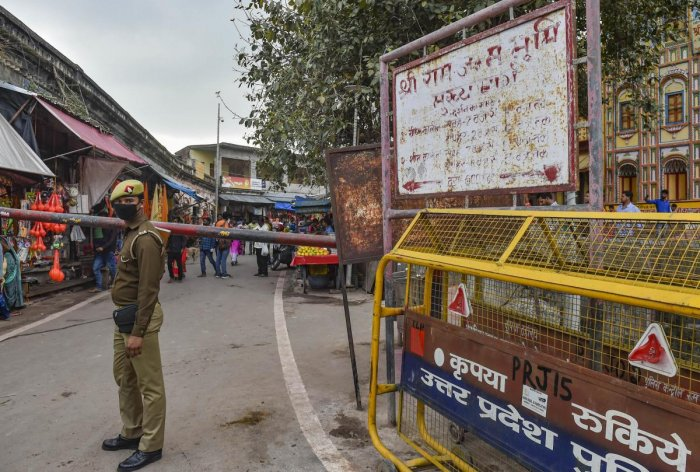 A police person wearing protective mask in the wake of coronavirus pandemic stands guard at a check-post near Ramlala market in Ayodhya, Saturday, March 14, 2020. (PTI Photo)