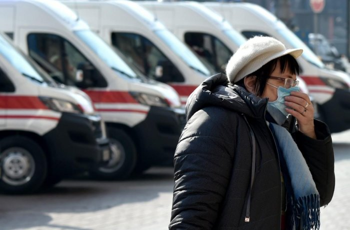 A woman adjusts her face mask as she walks past new ambulances parked in the center of the Ukrainian capital of Kiev on March 19, 2020. Credit: AFP Photo