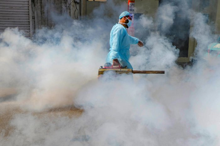 A Jammu Muncipal Corporation worker spray disinfectant on a street during Janta curfew in the wake of deadly coronavirus, in Jammu, Sunday, March 22, 2020. (PTI Photo)