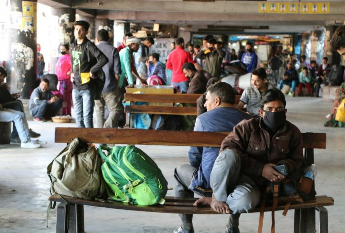 Stranded passengers sit as they look for public transport after authorities banned interstate bus service in the wake of coronavirus pandemic, in Jammu, Friday, March 20, 2020. (PTI Photo)