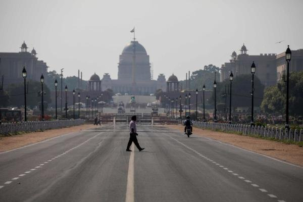 A man crosses a deserted Rajpath during a nationwide one day Janata (civil) curfew imposed as a preventive measure against the COVID-19 coronavirus in New Delhi on March 22, 2020. (Credit: AFP Photo)