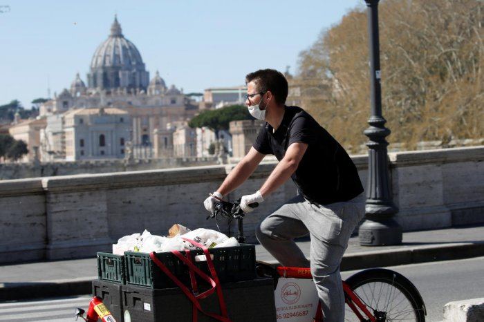 A delivery person passes near St. Peter's Basilica, as Italy tightens measures to try and contain the spread of coronavirus disease (COVID-19), in Rome. Credit: Reuters Photo