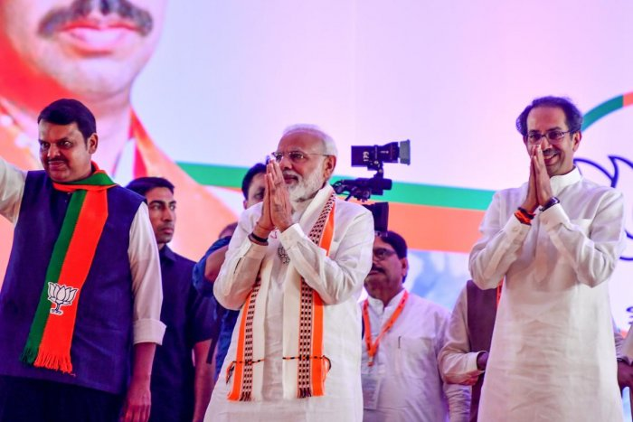 India's Prime Minister Narendra Modi (C) gestures along with Hindu right-wing party Shiv Sena Chief Uddhav Thackeray (R) and Chief Minister of the state Devendra Fadnavis (L) as they attend a public rally in the run up to the Maharashtra state assembly elections, in Mumbai on October 18, 2019. (AFP Photo)