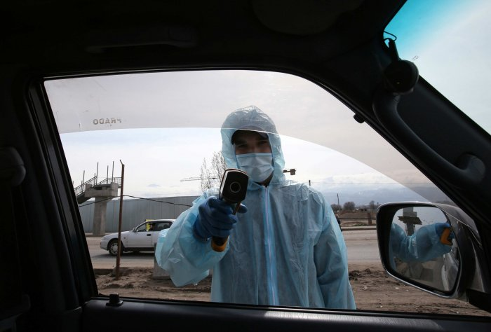 A medical official wearing protective gear takes the body temperature of passengers at a checkpoint set up to lock down the city to prevent the spread of coronavirus disease (COVID-19), on the outskirts of Almaty, Kazakhstan. (Credit: Reuters)