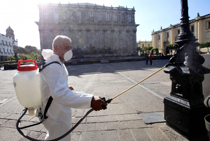 A worker wearing a protective suit sprays disinfectant during a campaign to sanitize public spaces as a preventive measure against the spread of the new coronavirus, COVID-19, in Guadalajara, Mexico. (Credit: AFP)