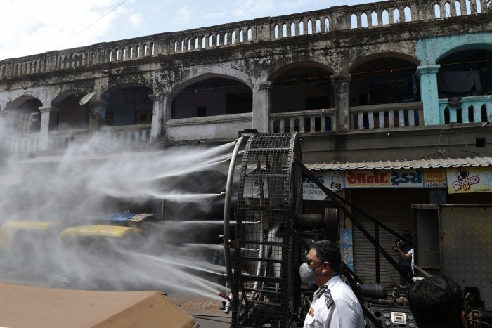 Firefighters from Ahmedabad Fire and Emergency Services spray disinfectant along a street during Gujarat's government-imposed lockdown. (Credit: AFP)