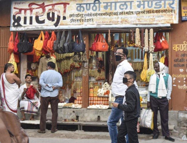 People wearing protective masks in the wake of coronavirus pandemic walk along Ramlala market in Ayodhya, Saturday, March 14, 2020. (PTI Photo)