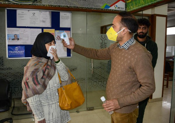 An official measures the temperature of a visitor using an infrared thermometer at the entrance of a bank, following the outbreak of coronavirus, in Srinagar, Monday March 23, 2020. (PTI Photo)