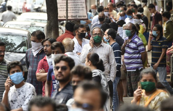 People stand in a queue to collect LPG cylinders during a 21-day nationwide lockdown in the wake of coronavirus pandemic, at Girgaon in Mumbai, Wednesday, March 25, 2020. (PTI Photo)