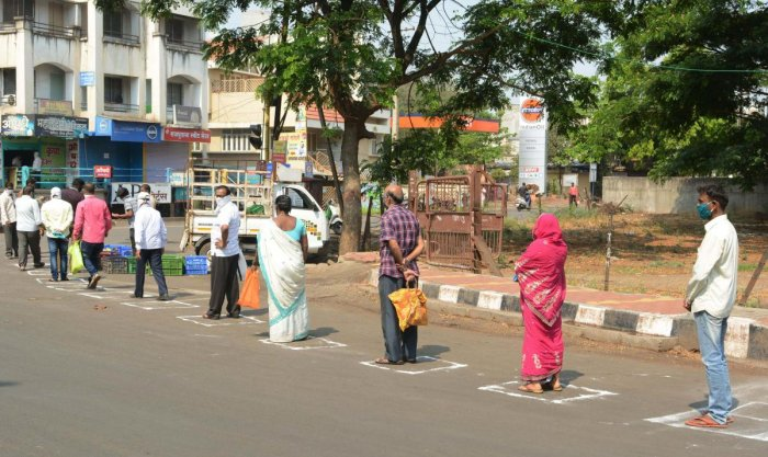 Customers stand one metre apart as a preventive measure against the novel coronavirus spread, while queuing up to buy vegetables, during total lockdown in Karad, Maharashtra. (PTI Photo)