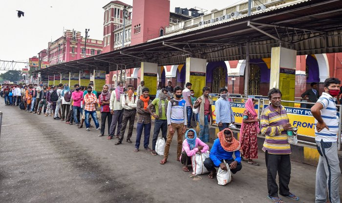 Stranded passengers at the Howrah Railway Station stand in a queue for free food, being distributed by a social organisation, during the complete lockdown imposed in the wake of coronavirus pandemic, in Kolkata. (Credit: PTI Photo)