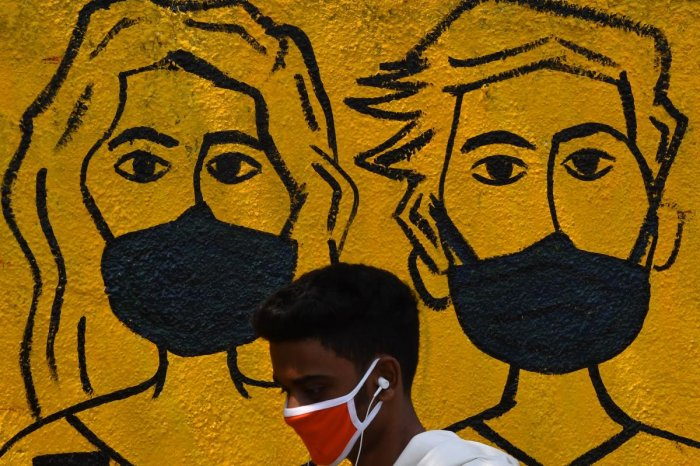 A youth wearing a facemask walk past a mural depicting people wearing famcemaks during the first day of a 21-day government-imposed nationwide lockdown as a preventive measure against the COVID-19 coronavirus, in Mumbai on March 25, 2020. Credit: AFP Photo