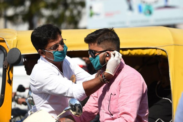 A volunteer of the Humf NGO adjusts a free facemask to a motorist during a facemaks donation campaing amid concerns over the spead of the COVID-19 coronavirus, in Ahmedabad on March 17, 2020. (AFP Photo)