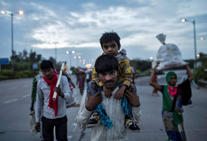 A migrant worker carries his son as they walk along a road with others to return to their village, during a 21-day nationwide lockdown to limit the spreading of coronavirus disease, in New Delhi. Credit: Reuters Photo