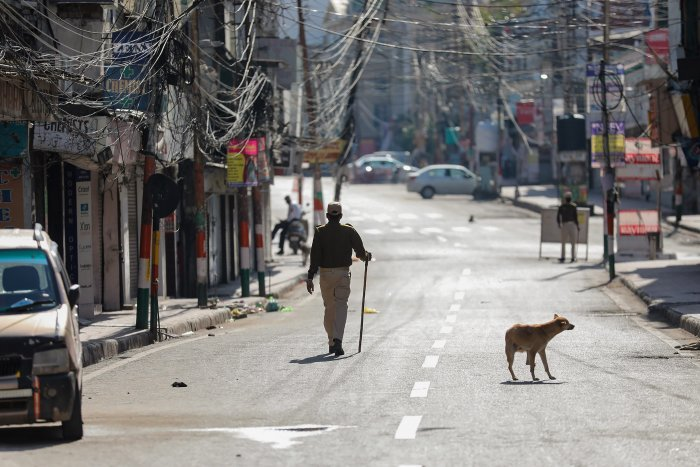 A policeman walks along a deserted road in Jammu. (PTI photo)