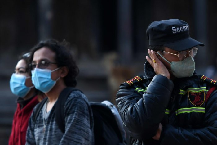 Visitors and a security guard wear facemasks as a preventive measure against the COVID-19 coronavirus at Patan durbar square in Lalitpur on March 17, 2020. Credit: AFP Photo