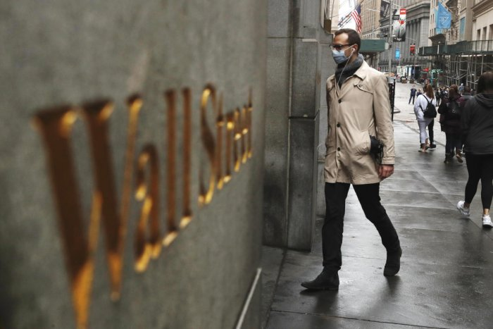 A man wears a protective mask as he walks on Wall Street during the coronavirus outbreak in New York. Credit Reuters File Photo