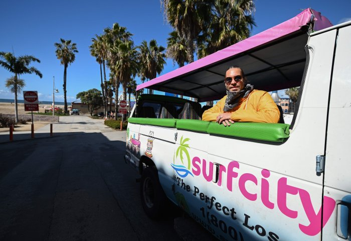 Adam Duford, owner of Surf City Tours, poses for a photo in one of his tour buses on an empty street near the beach in Santa Monica, California. (Credit: AFP)