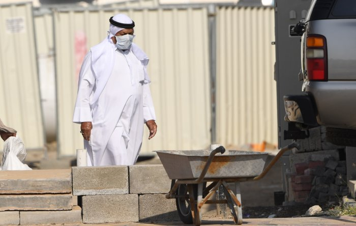 An Emirati man wearing a protective mask walks outside his house in Dubai. (Credit: AFP)