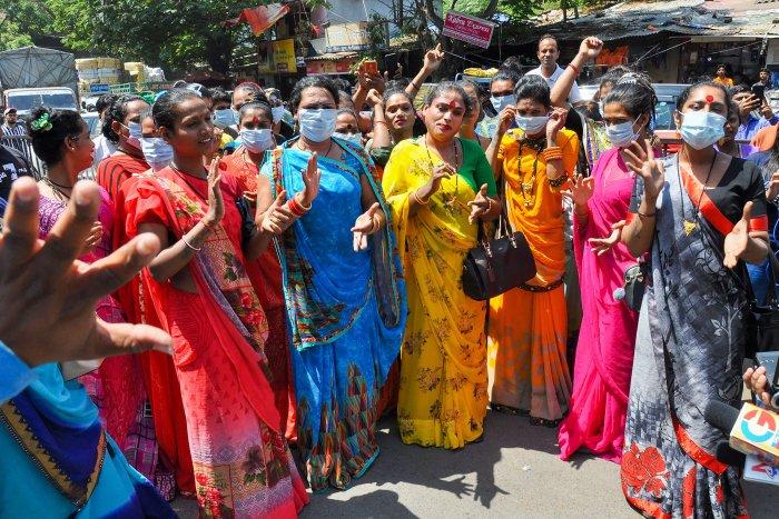 Members of the transgender community distribute masks to commuters to mitigate the coronavirus pandemic, in Surat. (PTI Photo)