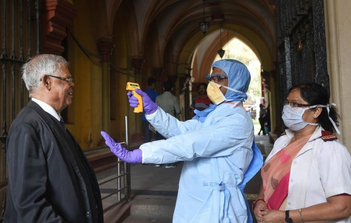 Thermal screening of lawyers being conducted in the wake of deadly coronavirus, at the entrance gate of Calcutta High Court in Kolkata, Tuesday, March 17, 2020. (PTI Photo)